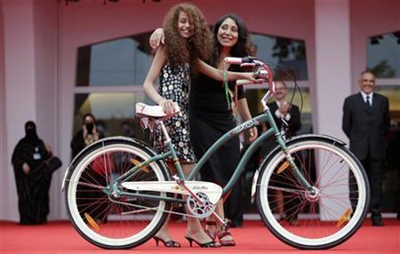 "Saudi Arabian director Haifaa al-Mansour and actress Waad Mohammed pose with a bicycle on the red carpet during the premiere screening of ""Wadjda"" during the 69th Venice Film Festival in Venice"